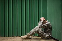 Frustrated military soldier sitting with hands on head in boot camp