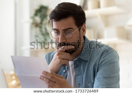 Frustrated millennial guy in glasses read bad unpleasant news in postal letter, sad confused young man consider paperwork get negative answer in post correspondence, eviction or dismissal notice