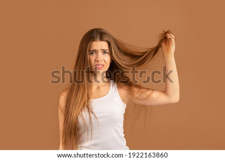 Frustrated millennial woman showing her damaged long locks on brown studio background. Pretty young lady having bad hair day, upset over her messy hairdo. Hairdressing services concept