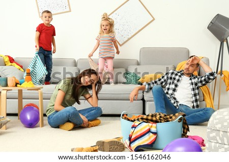 Frustrated parents and their mischievous children in messy room