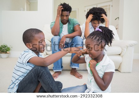 Frustrated parents watching their children fight at home in the living room