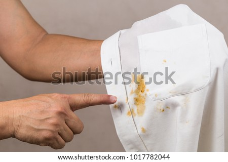 Frustrated person pointing to spilled curry stain on white shirt #1017782044