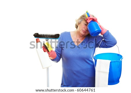 Frustrated retired woman holding many cleaning supplies