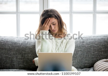 Frustrated sad woman feeling tired worried about problem sitting on sofa with laptop, stressed depressed girl troubled with reading bad news online, email notification about debt or negative message