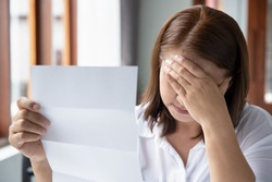 frustrated, shocked, stressed middle aged woman with expensive bill, debt invoice, eviction notice; concept of high cost of living, expensive bill, economic recession, no job no money