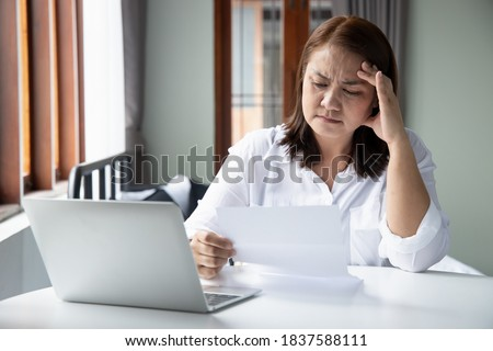 frustrated, shocked, stressed middle aged woman with expensive bill, debt invoice, eviction notice; concept of high cost of living, expensive bill, economic recession, no job no money Photo stock ©