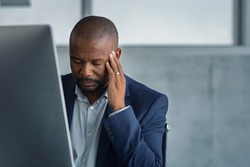Frustrated stressed business man sitting at desk. Tired mature businessman at workplace with terrible headache. African american boss working at computer with burnout syndrome at desk with copy space.