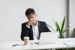 Frustrated stressed businessman feeling tired of computer work sitting at workplace, exhausted man in suit suffers from eye strain or blurry vision problem after long laptop use, eyes fatigue concept