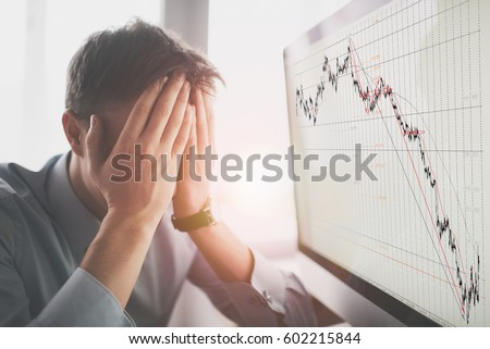 Frustrated stressed shocked business man with financial market chart graphic going down on grey office wall background. Poor economy concept. Face expression, emotion, reaction