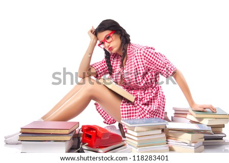 Frustrated Student with books - Attractive female student sitting behind a large pile of books with a stressed and burnt out look on her face. Red vintage dress, large nerdy glasses, white background