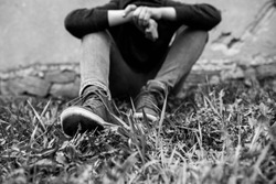 Frustrated teenage boy sitting near a crumbling wall at the correctional institute, focus on the boys shoe, in black and white.