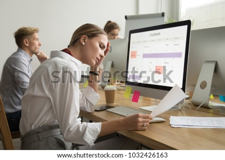 Frustrated tired businesswoman reading document with bad news, corporate employee stressed by mistake in paperwork, troubled with problem, upset about dismissal notice or feeling headache at work