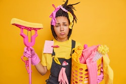 Frustrated unhappy housewife has sulking face expression has tired exhausted expression after cleaning house carries laundry basket and mop isolated over yellow background. Housekeeping concept