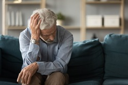 Frustrated unhappy middle aged mature man sitting on sofa, feeling depressed alone at home. Confused senior retired grandfather worrying about difficult life decision, copy space, old people solitude.