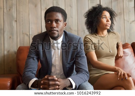 Frustrated upset african couple in quarrel sitting on sofa not talking after fight, stubborn disappointed black man ignoring sad depressed offended woman, problem in marriage relationships concept #1016243992