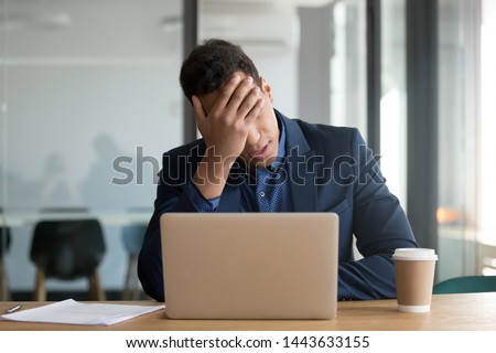 Frustrated upset black business man stressed about computer problem, bad online news financial market crisis, sad desperate african ceo feel loser sit at desk with laptop shocked by bankruptcy debt