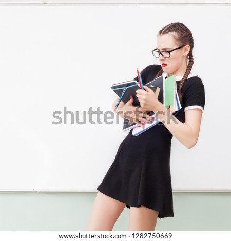 Frustrated upset college girl joggling with stack of text books in front of school board - back to school - Too stressed education or teaching in high school university concept