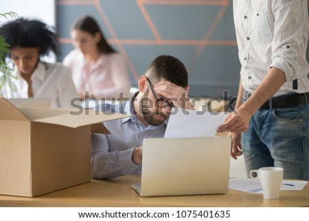 Frustrated upset male employee receiving unfair dismissal notice getting fired from job at workplace, depressed stressed office worker about to pack box on last working day being laid off concept