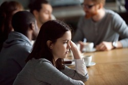 Frustrated upset millennial girl sitting alone at cafe table after conflict ignoring friends, young woman feeling jealous rejected offended thinking of bad relations with boyfriend in public place