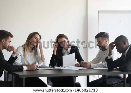 Frustrated upset multiracial business team people sad with bad work result in report disappointed in corporate bankruptcy failure crisis worried of paperwork problem sit at table at office meeting