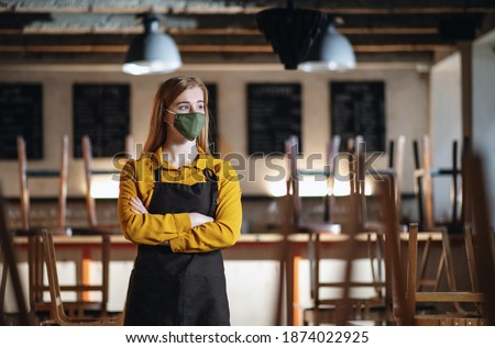 Frustrated waiter standing in closed cafe, small business lockdown due to coronavirus.
