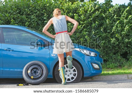 Frustrated Woman Broken Down With Flat Tyre On Car