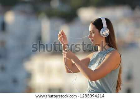 Frustrated woman fighting with the headphones cord in the street #1283094214