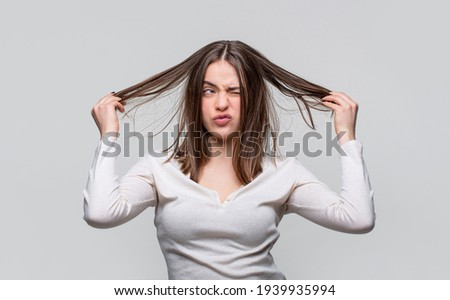 Frustrated woman having a bad hair. Woman having a bad hair, her hair is messy and tangled. Messy hair. Brunette woman with messed hairs. Girl having a bad hairs. Bad hairs day.