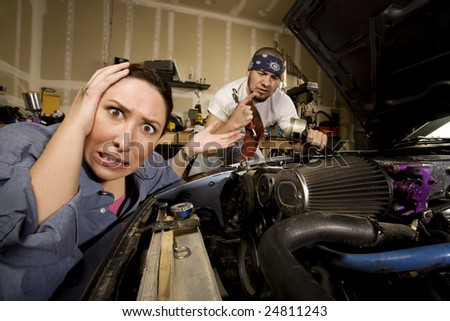 Frustrated woman leaning on car with incompetent male mechanic in background