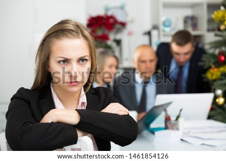 Frustrated woman sitting at office on background with coworkers