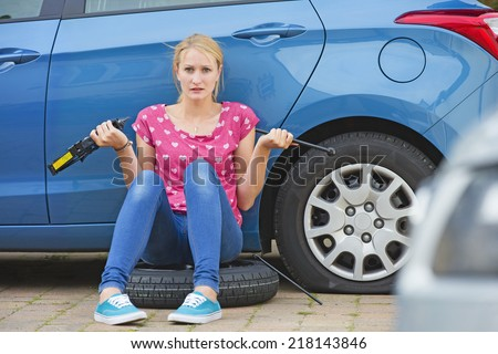 Frustrated Woman Trying To Change Flat tire On Car