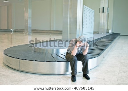 frustrated woman with lost luggage look upset sitting at the baggage carousel at an airport - concept of airline travelers troubles when baggage not arriving at destination with the flight