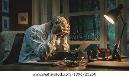 Frustrated writer experiencing a creative slowdown, he is sitting at desk and typing on a vintage typewriter Photo stock ©