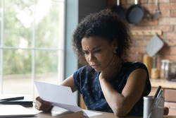 Frustrated young african american woman reading paper letter with bad news, stressed of getting bank debt or loan rejection notification, feeling confused of termination notice, sitting at table.