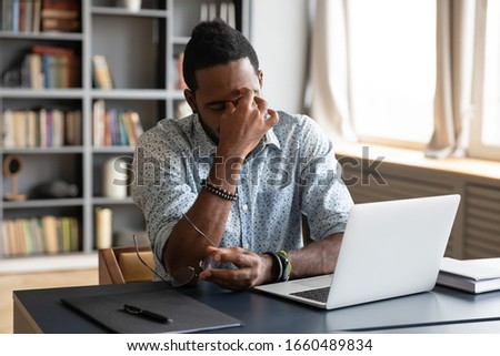 Frustrated young biracial guy taking off eyeglasses, massaging nose bridge, feeling tired due to computer overwork. Overwhelmed stressed millennial african american man suffering from eyes strain.