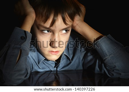 frustrated young boy on a black background