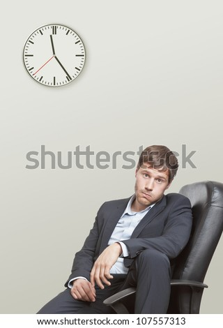 Frustrated young business man waiting for the end of the workday