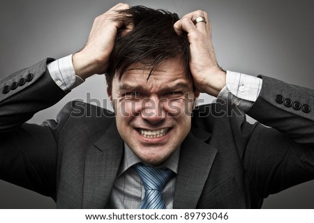 Shutterstock Frustrated young businessman pulling his hair, studio shot