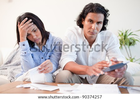 Frustrated young couple checking their bills in the living room