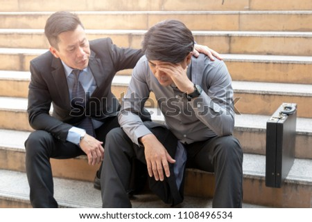 Frustrated young man being consoled by his friend in city. young businessman consoling encouraging friend. Comforting a work colleague.