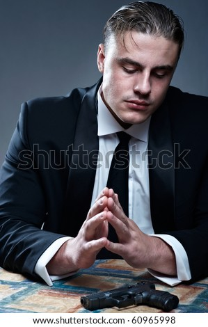 Frustrated young man in suit preparing for suicide. Black gun on table.