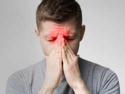 Frustrated young man suffering from sinus pressure, touching his nose with closed eyes