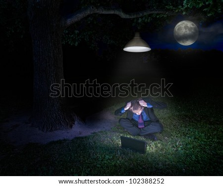 Frustrated young man with laptop in forest under the lamp at night