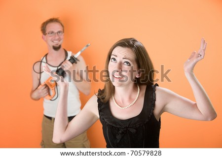 Frustrated young woman and handy husband with reciprocal saw