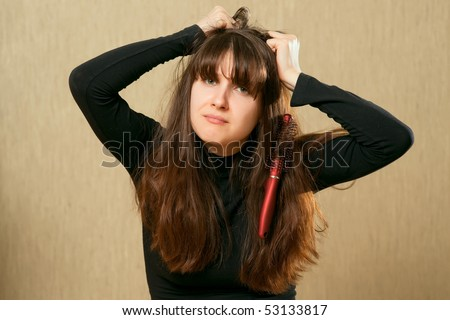 Frustrated young woman having a bad hair day with brush stucks in her hair