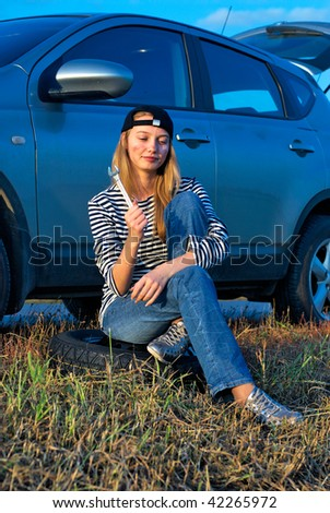 Frustrated young woman with wrench near broken car