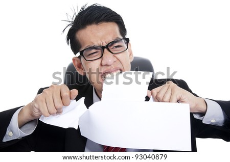 Frustration businessman tearing documents with his hands and teeth