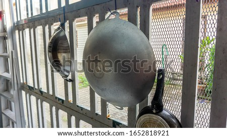 Fry pan and metal woks hanging on the wall at the kitchen to dry it after clean it during the dishes.