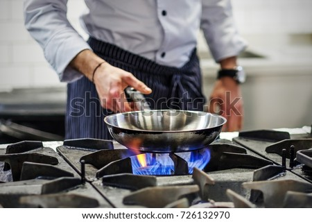 Frying pan on a gas stove. Chef controls the cooking process