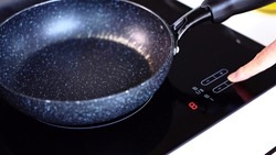 Frying pan on induction cooker in kitchen.